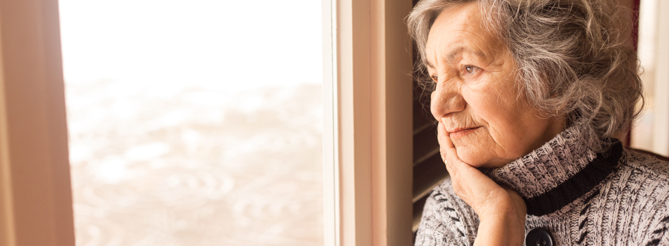 Woman looking out window at winter scene